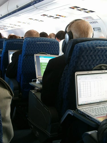 row of laptops on a plane